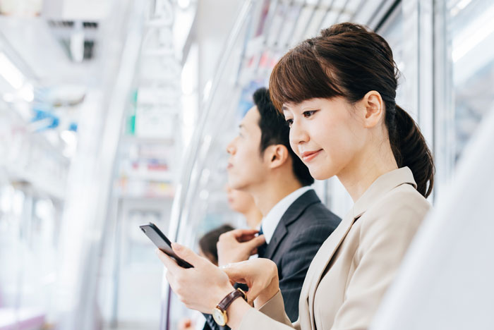 電車でスマホを見ている女性