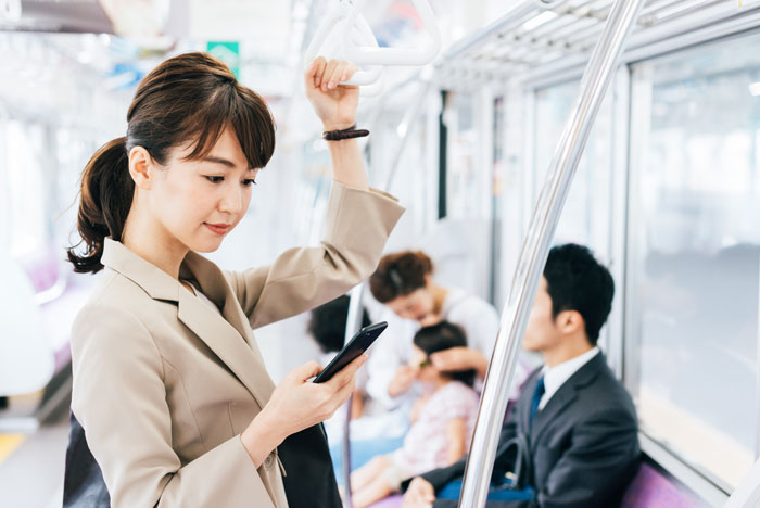 電車に乗りながらスマホを見ている女性