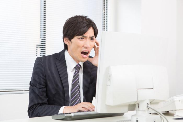 パソコンの前でショックを受けている男性