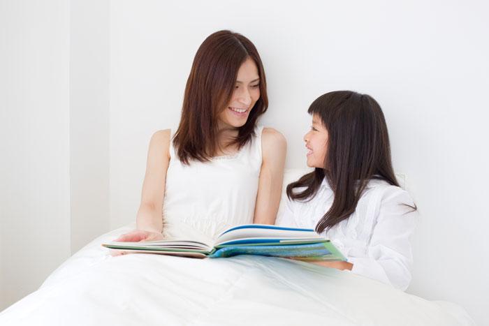 ベッドで子どもに絵本を読む母親