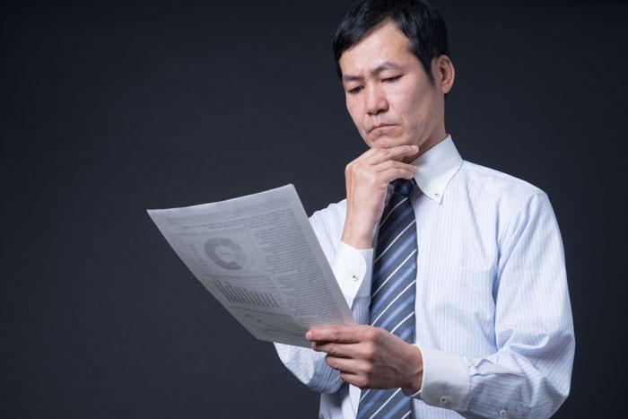 渋い顔で書類をにらむ男性