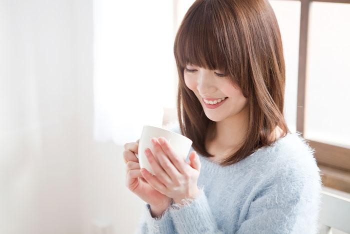 美味しそうにコーヒーを飲んでいる女性