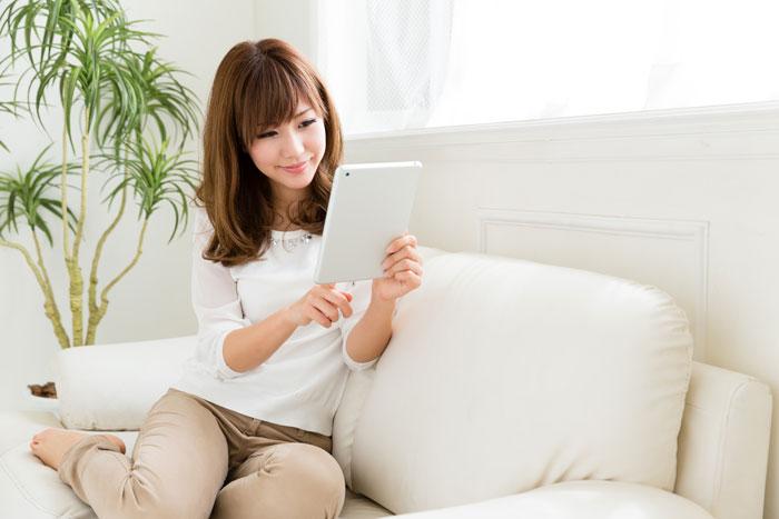 自宅でタブレットを見る女性