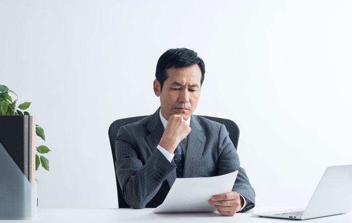 書類を睨んでいる中年男性