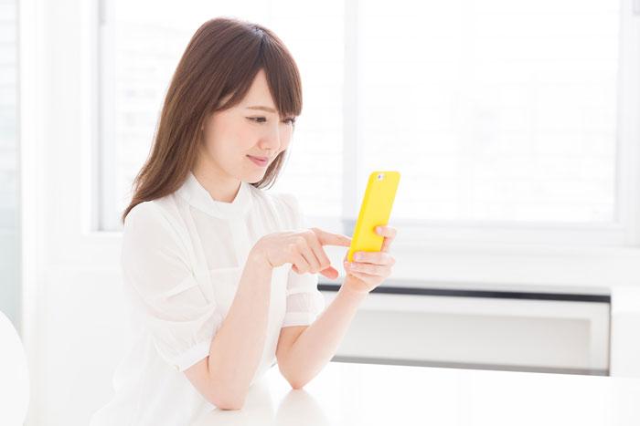 自宅でスマホをチェックしている若い女性