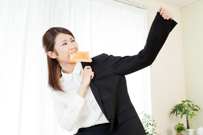 急いでパンを食べている女性
