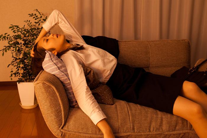 自宅のソファに倒れ込むスーツ姿の女性