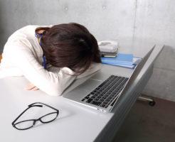 パソコンの前でショックを受けて倒れ込んでいる女性