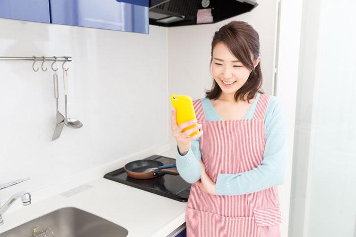 キッチンでスマホを操作する女性