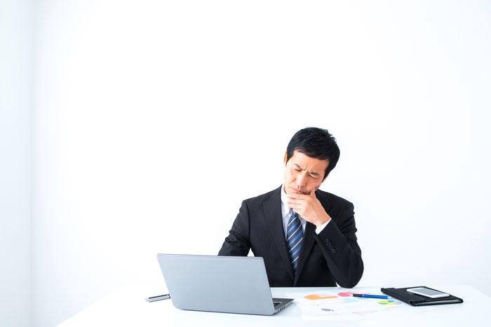 パソコンの前で考え込んでいる男性