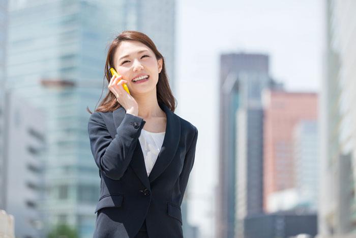 電話をしながら歩くスーツ姿の女性