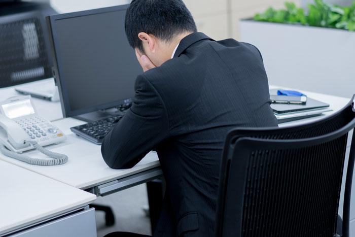 オフィスのデスクでショックを受けている男性