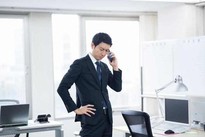 悩みながら電話をかけている男性