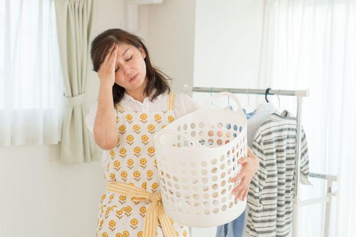 洗濯物を干しながら頭を抱える女性