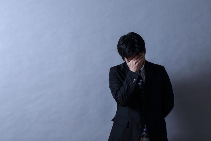 ストレスを抱えているスーツ姿の男性