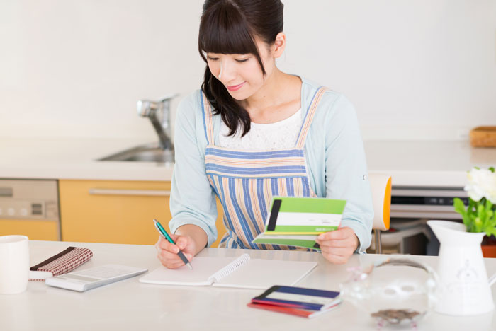 自宅で家計簿をつけている女性