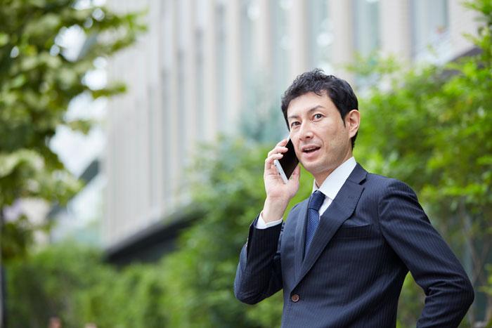 屋外で電話中の中年男性