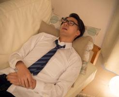 疲れ果ててソファで寝る男性