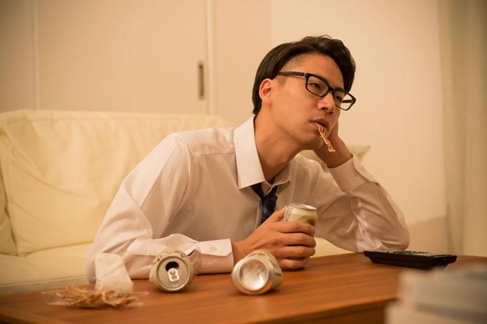 自宅でやけ酒を飲んでいる男性