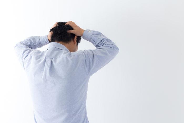 ショックで頭を抱える男性