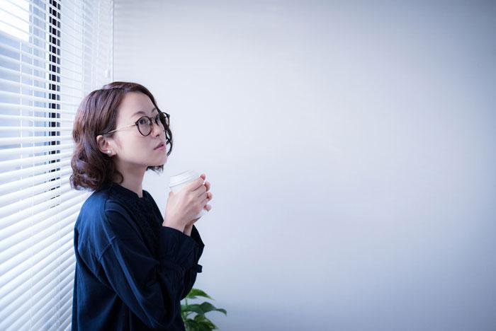 会議室でコーヒーを飲んでいる女性