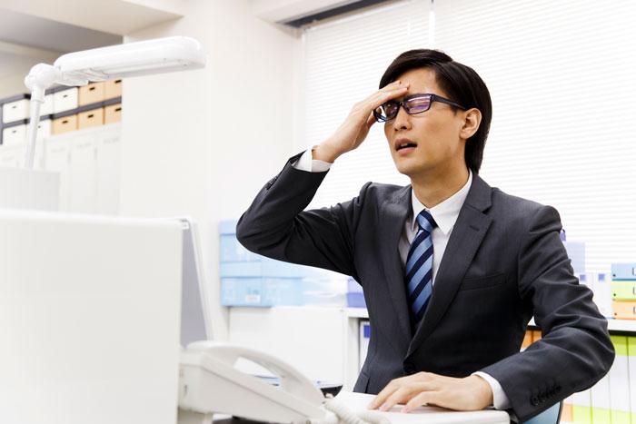 パソコンの前で頭を抱える眼鏡の男性