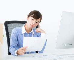 険しい表情で書類を見つめる女性