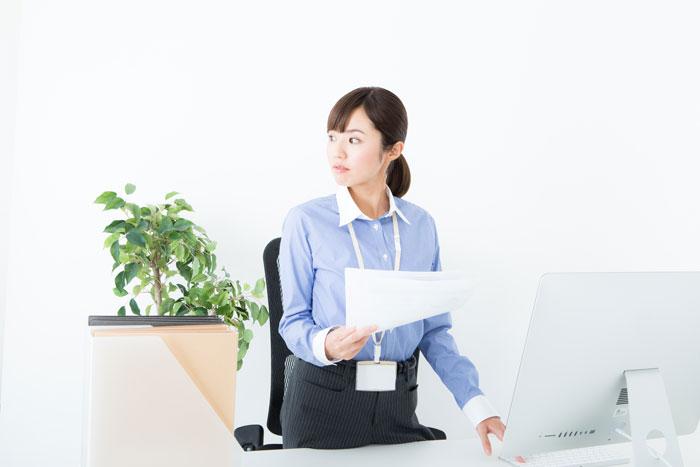 オフィスで書類をチェックしている女性