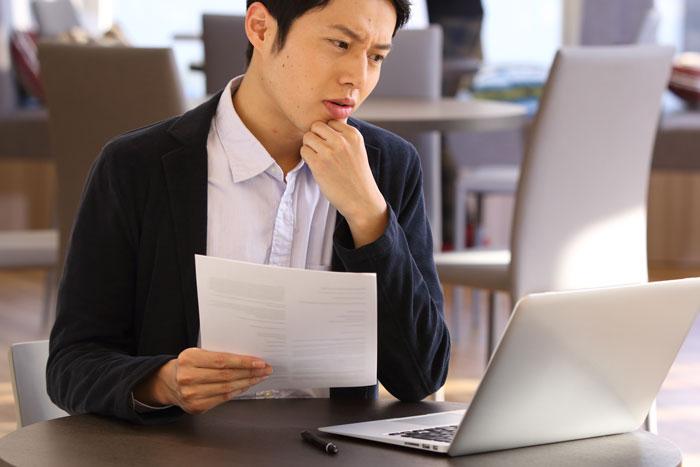 険しい顔でパソコンを見つめる男性