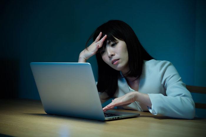 パソコンの前で疲れ切っている女性