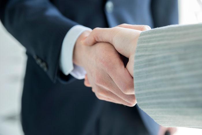 ガッチリ握手を交わすスーツの男女