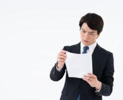 書類を睨んでいるスーツ姿の男性