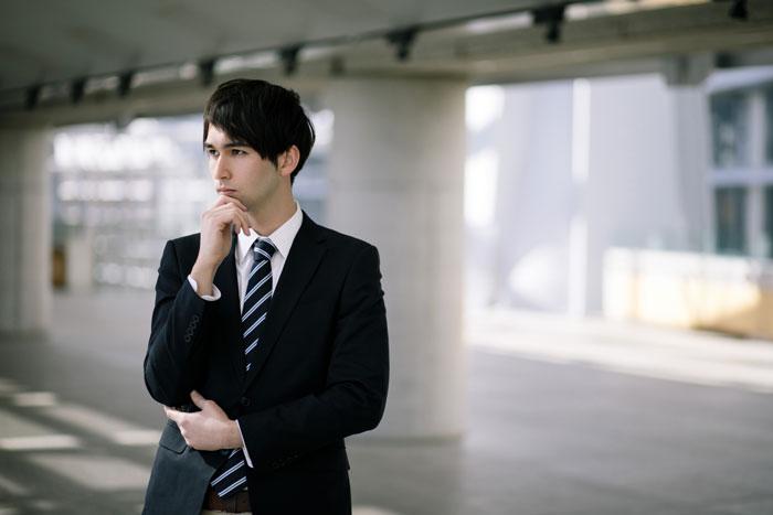 転職について悩んでいる男性