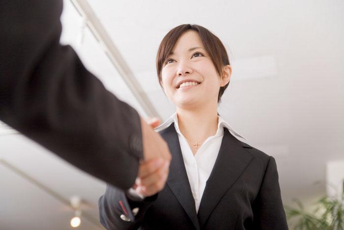 笑顔で握手を交わすスーツ姿の女性