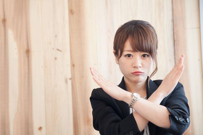 腕でバツマークを作る若い女性