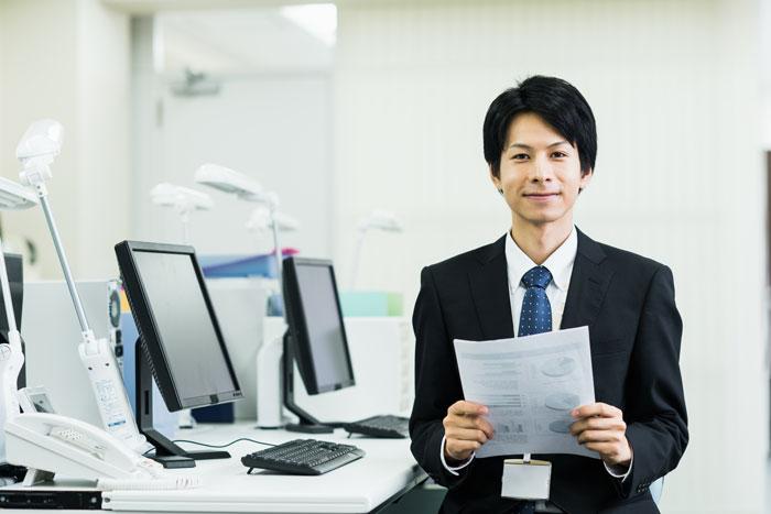 書類を持っているスーツ姿の男性