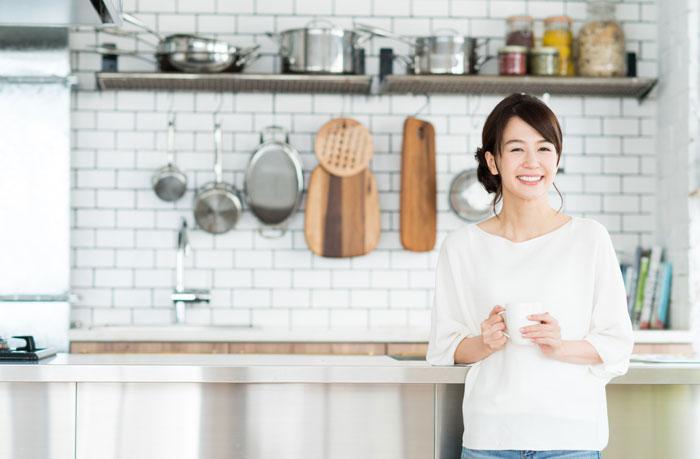 おしゃれなキッチンでコーヒーを飲む女性