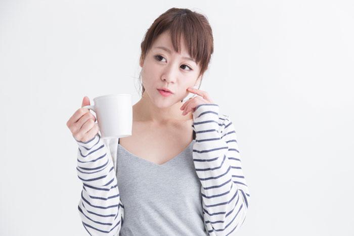 コーヒーを飲みながら考え込んでいる女性