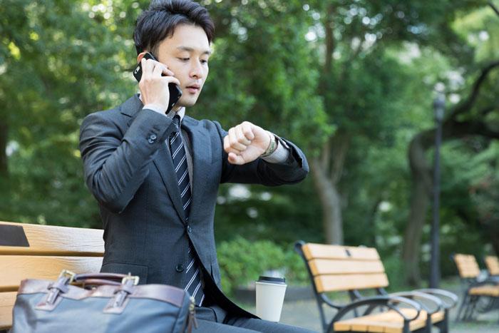 外で電話をしている男性