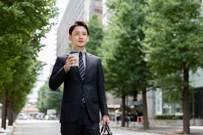 コーヒー片手に歩く男性社会人