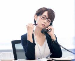 不機嫌な表情で仕事をする女性