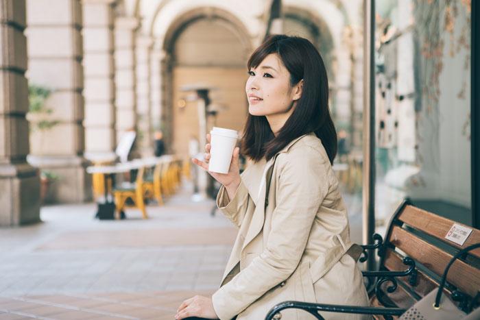 ベンチでコーヒーを飲んでいる女性