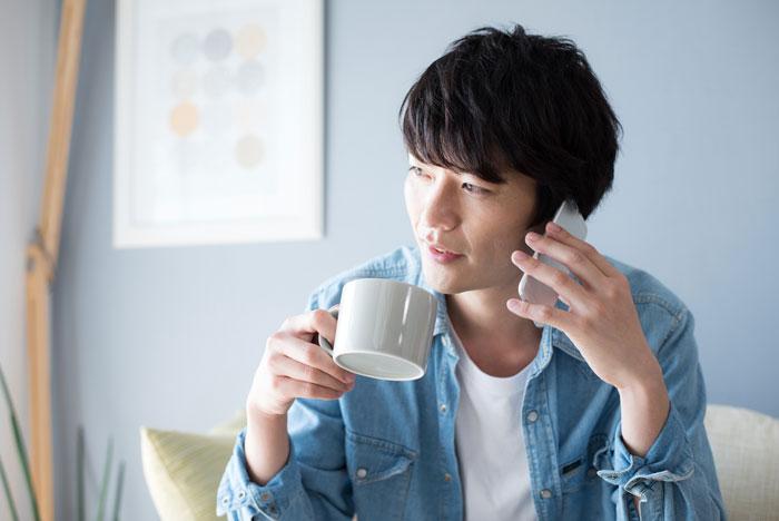 自宅でコーヒーを飲んでいる男性