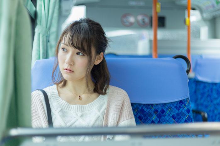 バスに乗って移動中の女性