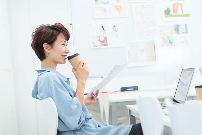 コーヒーを飲みながら働く女性