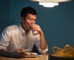 自宅で缶ビールを飲んでいる男性