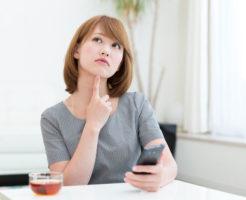 自宅で考え事をしている若い女性
