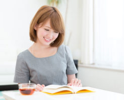 自宅で本を読んでいる若い女性