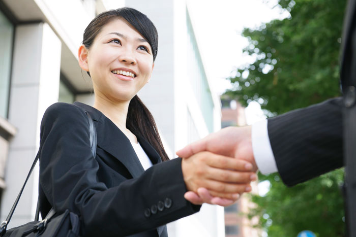 固く握手を交わすスーツ姿の女性