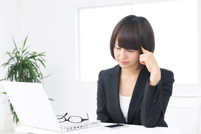 パソコンの前で悩んでいる若い女性